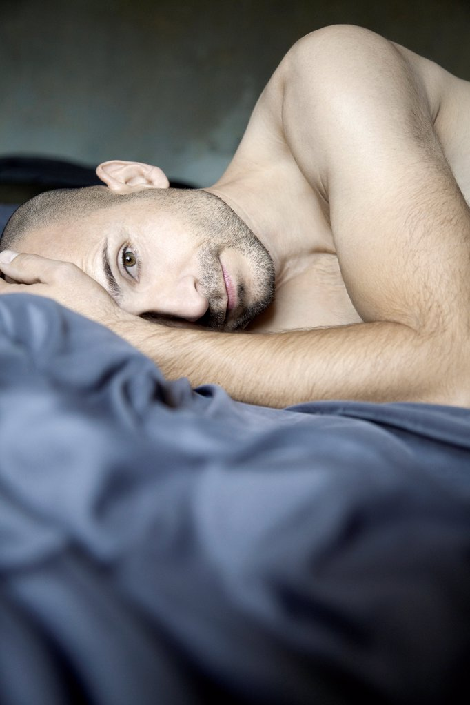 Stock Photo: 1841R-125076 Barechested man with designer lying in bed
