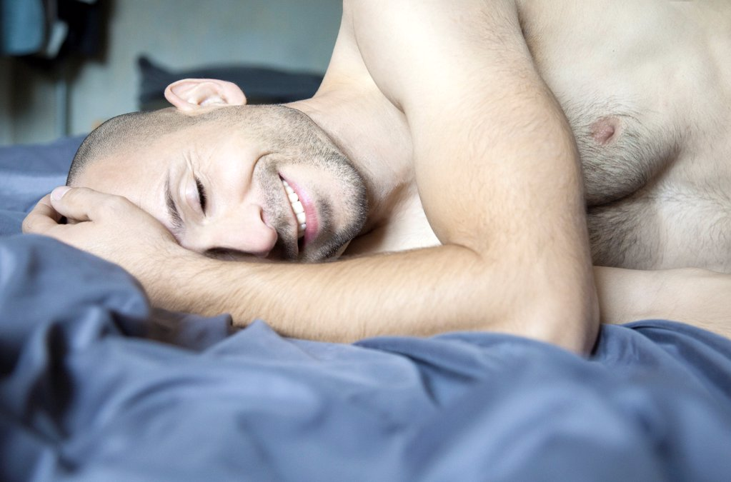 Stock Photo: 1841R-125077 Smiling barechested man with designer stubbles on bed