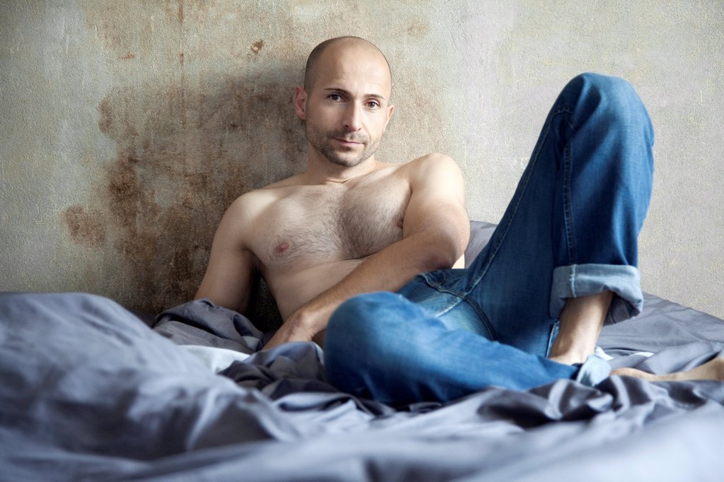 Barechested man with designer stubbles on bed : Stock Photo