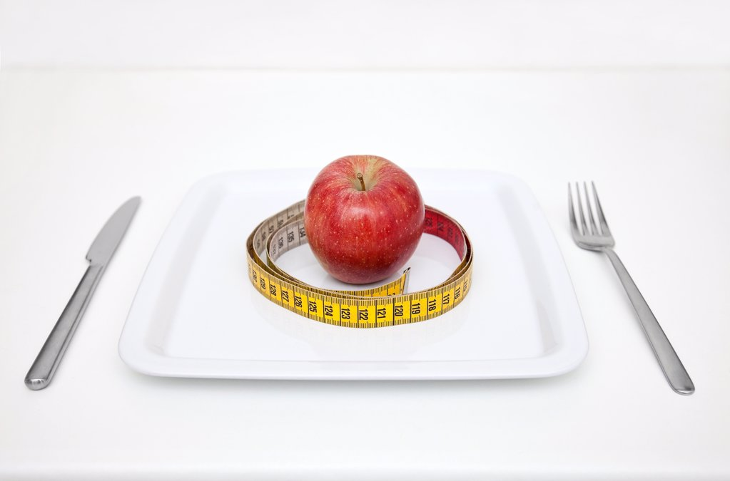 Plate with apple and tape measure : Stock Photo