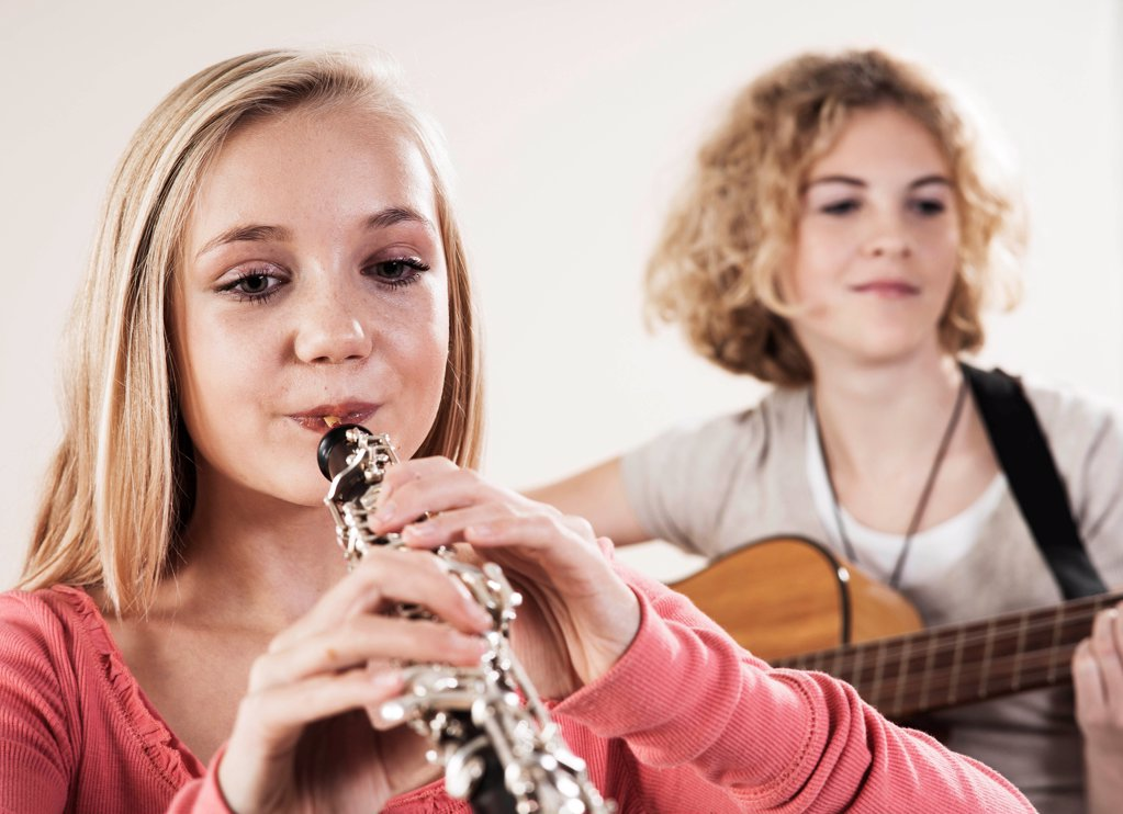 Stock Photo: 1841R-125137 Two teenage girls playing guitar and oboe