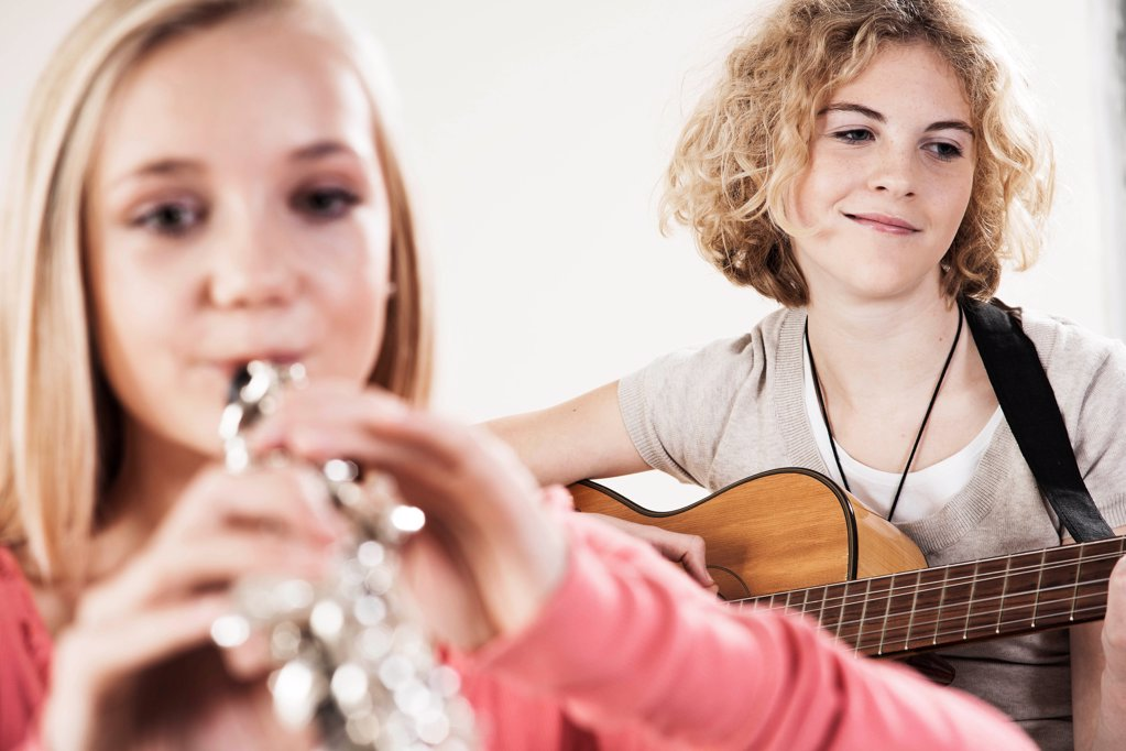 Stock Photo: 1841R-125138 Two teenage girls playing guitar and oboe