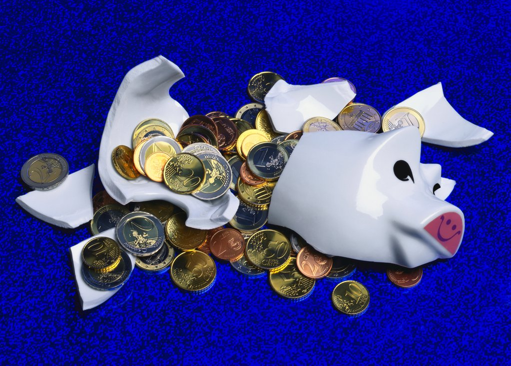 Broken Piggy bank with scattered coins : Stock Photo