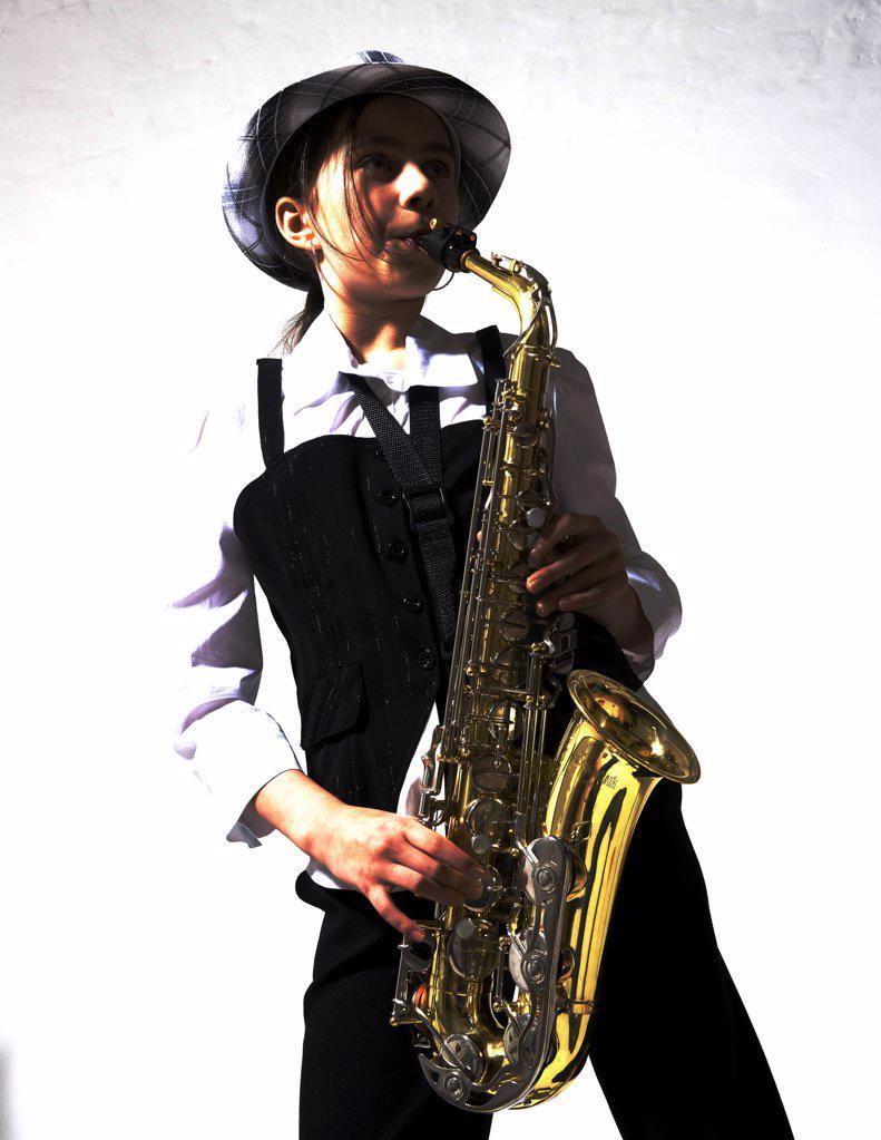 Girl playing saxophone : Stock Photo