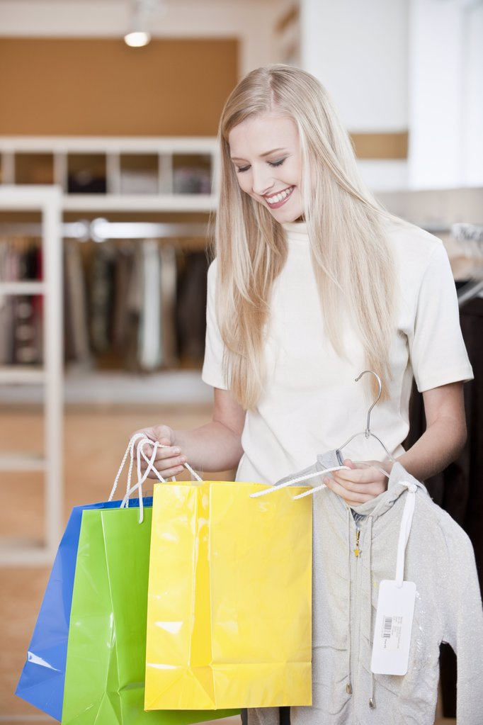 Young woman in fashion boutique holding shopping bags, three quarter length : Stock Photo