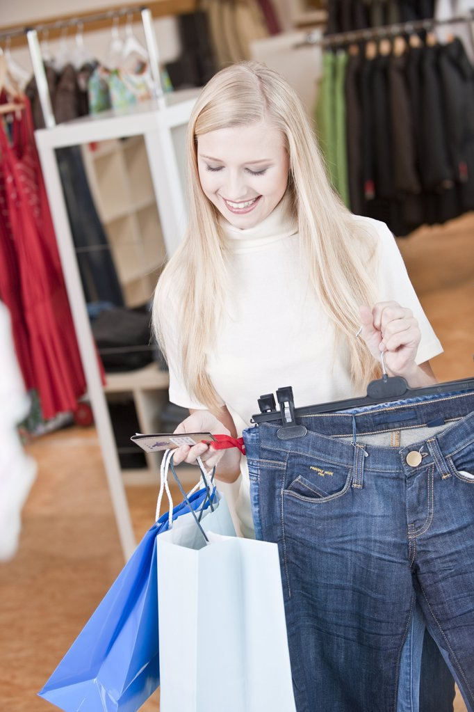 Young woman in a store looking at the price label of a jeans, high angle view : Stock Photo