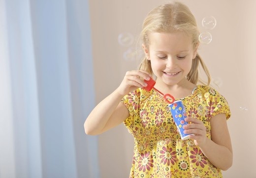 Stock Photo: 1841R-83026 Young girl making soap bubbles, waist up