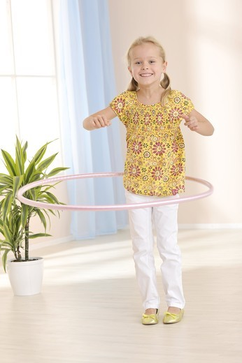 Stock Photo: 1841R-83032 Girl practising with hula hoop, slanted view