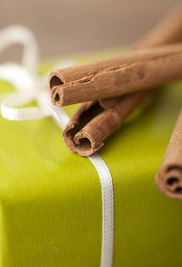 Cinnamon sticks on a wrapped present, detail : Stock Photo
