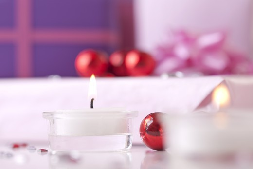Stock Photo: 1841R-83082 Burning Tealights, baubles and wrapped gifts in the background, surface level, close-up