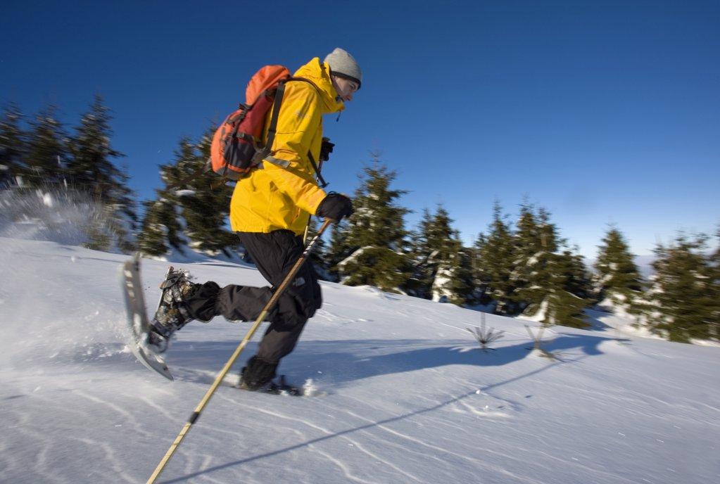 Junger Mann l‰uft unter blauen Himmel mit Schneeschuhen in Winterlandschaft : Stock Photo