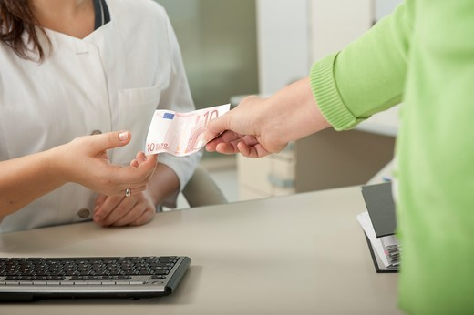 Female patient handing over ten Euro to doctor's assistant at desk : Stock Photo