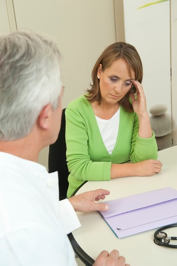 Depressed woman at the doctor : Stock Photo