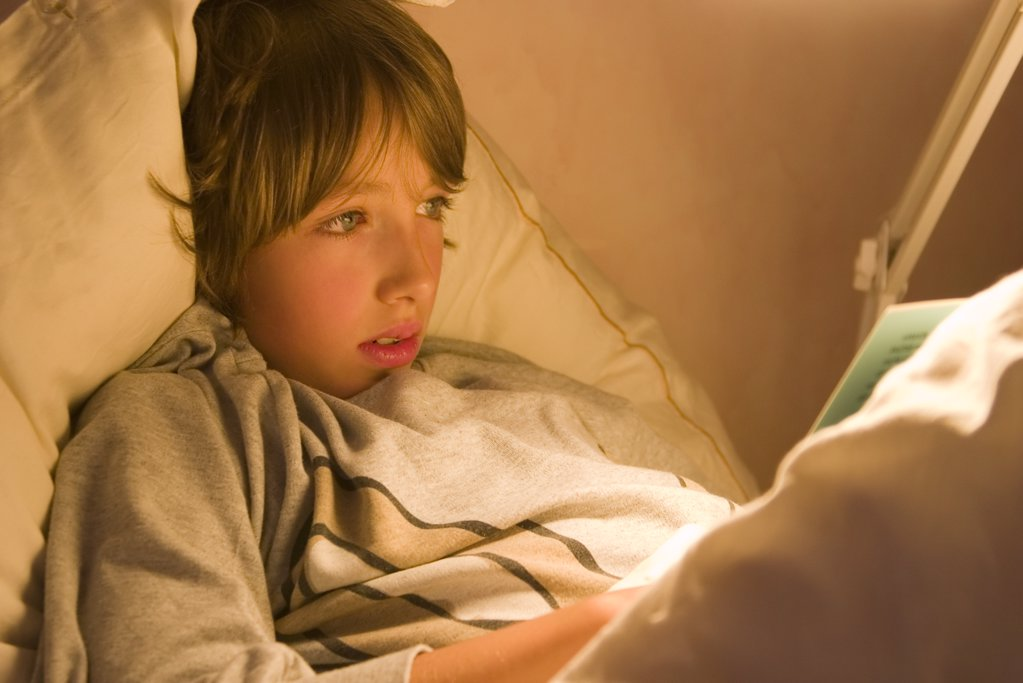 Stock Photo: 1841R-86444 Close-up of boy reading book on bed