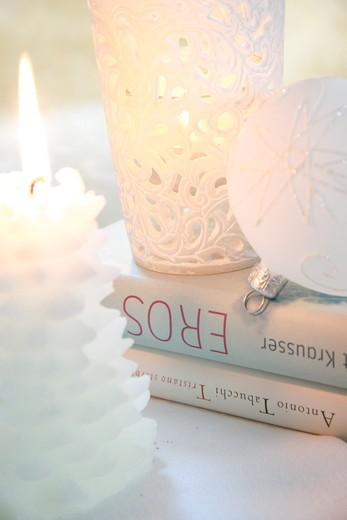 Close-up of Christmas ornament with burning candle and books : Stock Photo