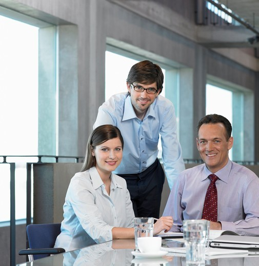 Portrait of three businesspeople smiling in meeting : Stock Photo