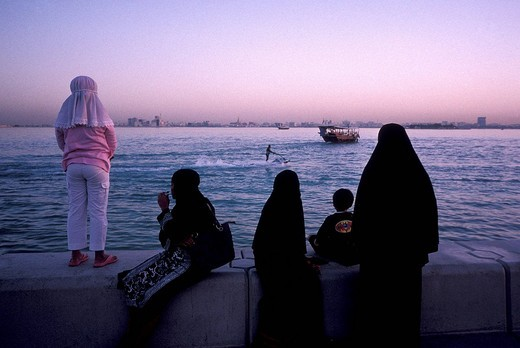 Women in traditional Abbeya dress with their chidlren overlooking Doha bay, Doha, Qatar, Middle East : Stock Photo
