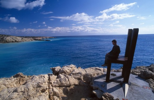 Stock Photo: 1844-5061 Russian immigrant Andreas sitting on the huge chair that he constructed in the southern point of Europe  Trypiti cape  Gavdos Island  Crete, Greece