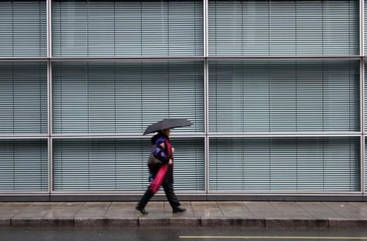 Rue des Alpes street, woman walking under rain  Geneva, Switzerland, Europe : Stock Photo
