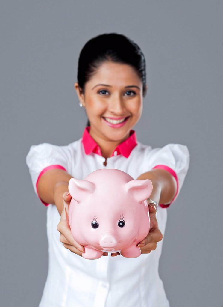 Stock Photo: 1845R-6920 Portrait of a woman holding a piggy bank