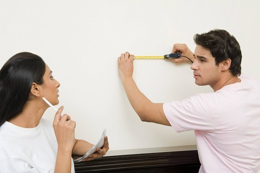 Couple measuring the wall with a tape measure : Stock Photo