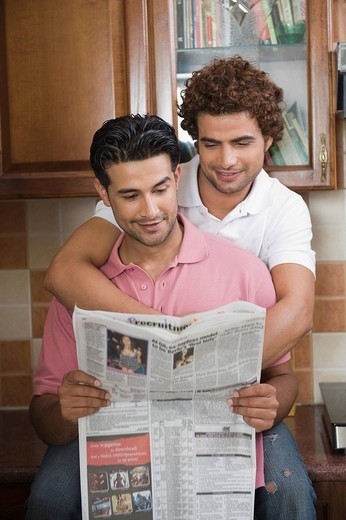 Stock Photo: 1846-10230 Gay couple reading a newspaper in the kitchen