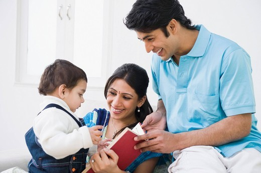 Stock Photo: 1846-10681 Couple showing a book to their son
