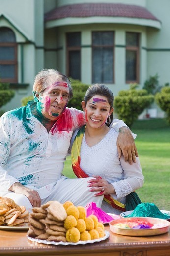 Woman celebrating Holi with her father : Stock Photo