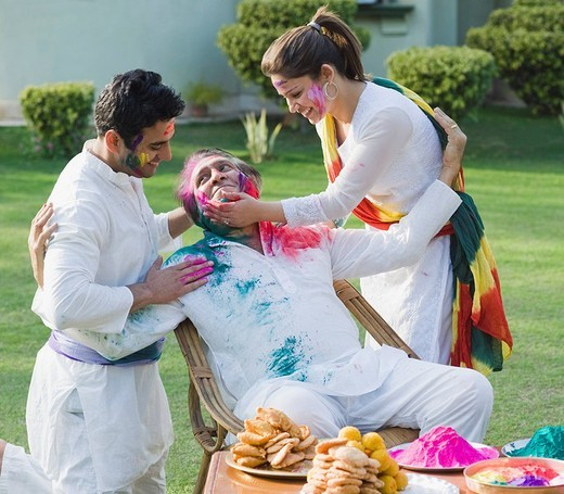Family celebrating Holi : Stock Photo