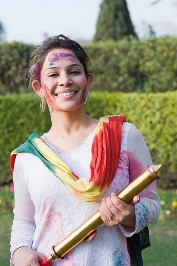 Stock Photo: 1846-10805 Woman holding a pichkari and celebrating Holi