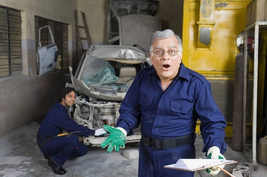 Portrait of an auto mechanic gesturing with an apprentice repairing a car in the background : Stock Photo