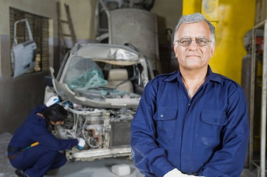 Portrait of an auto mechanic with an apprentice repairing a car in the background : Stock Photo