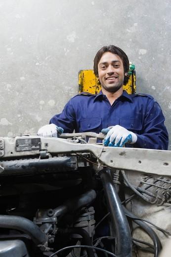 Auto mechanic repairing a car in a garage : Stock Photo