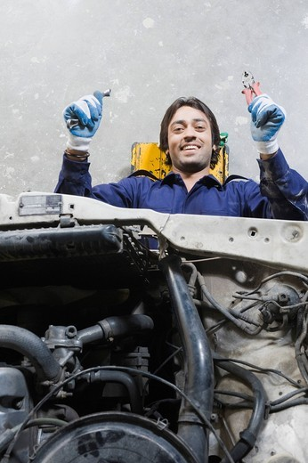 Auto mechanic repairing a car in a garage : Stock Photo