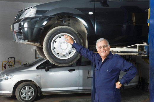 Auto mechanic leaning against a car : Stock Photo