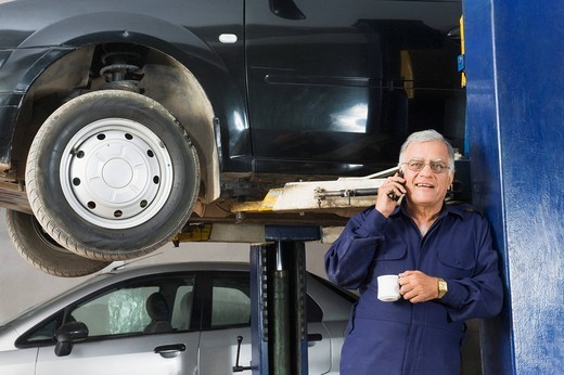 Stock Photo: 1846-10968 Auto mechanic talking on a mobile phone while drinking coffee in a garage