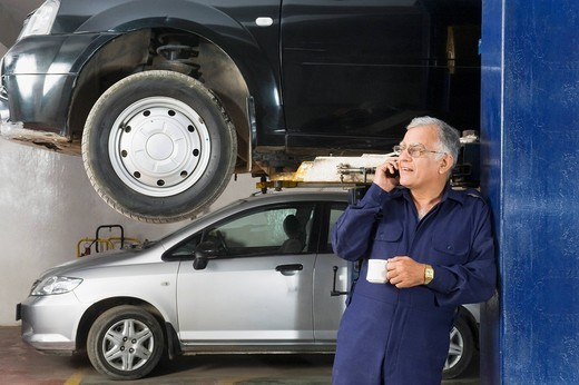 Auto mechanic talking on a mobile phone while drinking coffee in a garage : Stock Photo