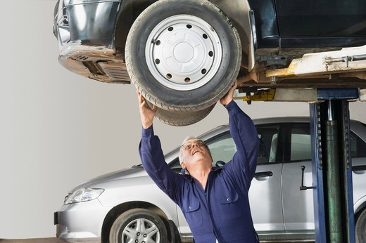 Auto mechanic working on a car wheel in a garage : Stock Photo