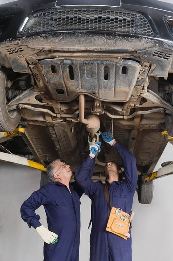 Auto mechanic with an apprentice working under a raised car in a garage : Stock Photo