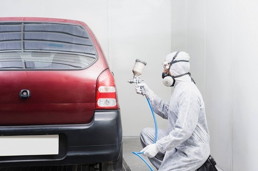 Auto mechanic painting a car in a garage : Stock Photo
