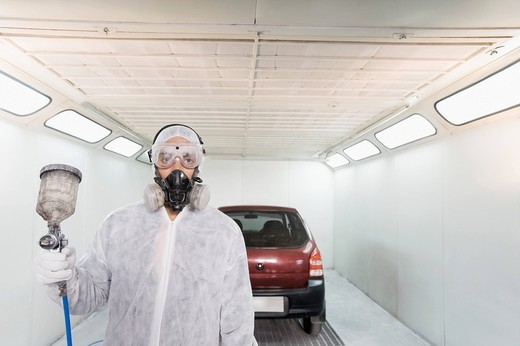 Auto mechanic holding a paint spray gun in a garage : Stock Photo
