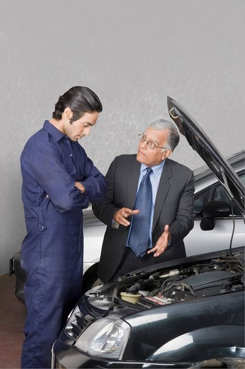 Customer explaining car problems to the auto mechanic : Stock Photo