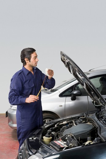 Auto mechanic wiping oil from a car dipstick in a garage : Stock Photo