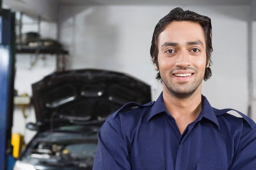 Portrait of an auto mechanic smiling with a car in the background : Stock Photo