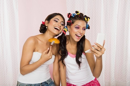 Two women applying make_up : Stock Photo