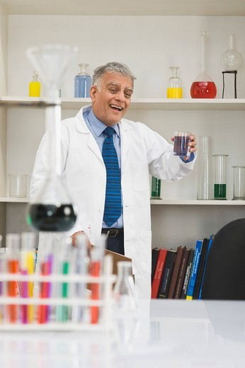 Scientist doing scientific experiment in a laboratory and smiling : Stock Photo