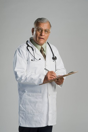 Portrait of a doctor writing on a clipboard : Stock Photo
