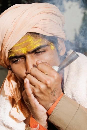 Stock Photo: 1846-11608 Close_up of a sadhu smoking a chilam, Haridwar, Uttarakhand, India
