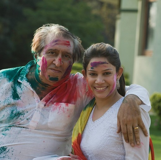Portrait of a woman celebrating Holi with her father : Stock Photo
