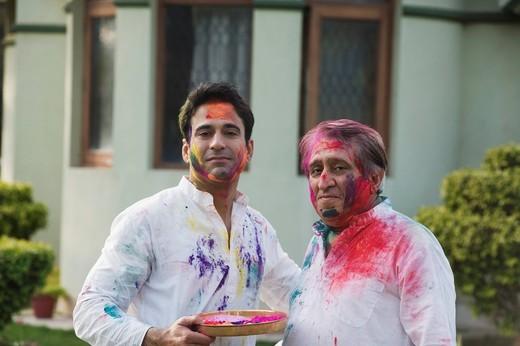 Man celebrating Holi with his son : Stock Photo